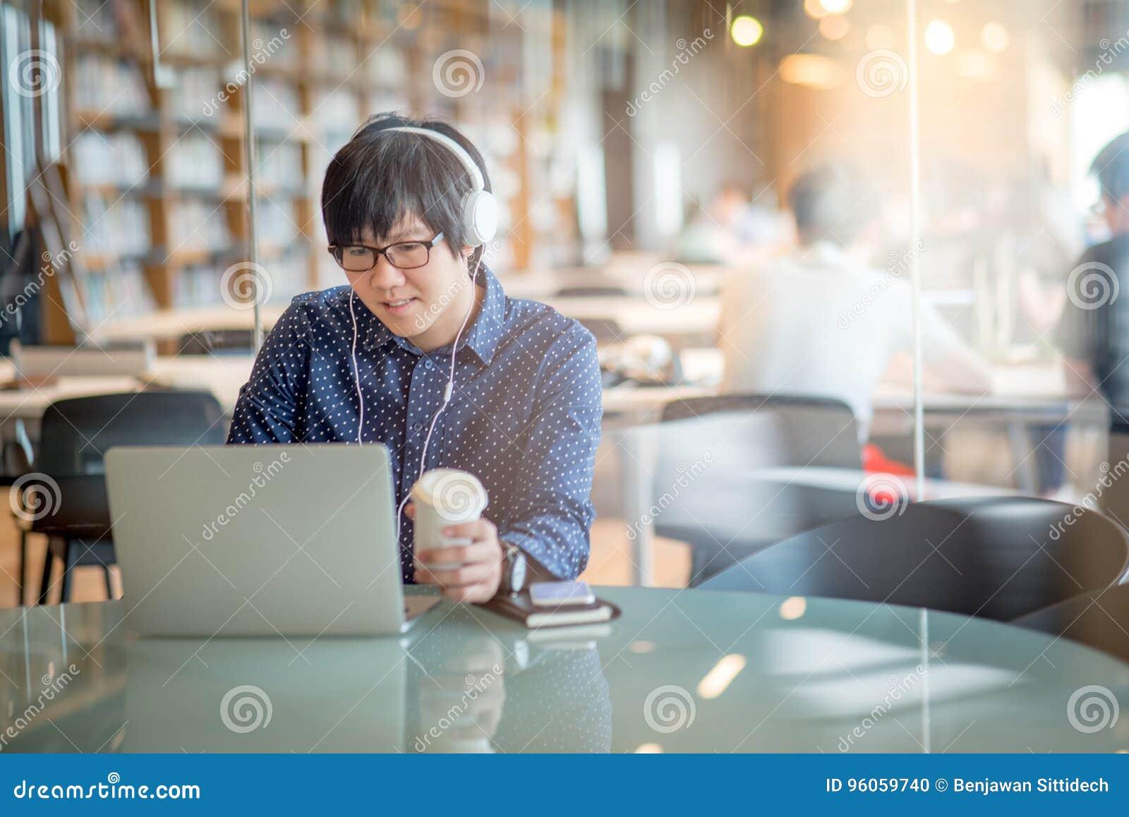 Jeune homme asiatique travaillant avec l ordinateur portable dans la bibliothèque