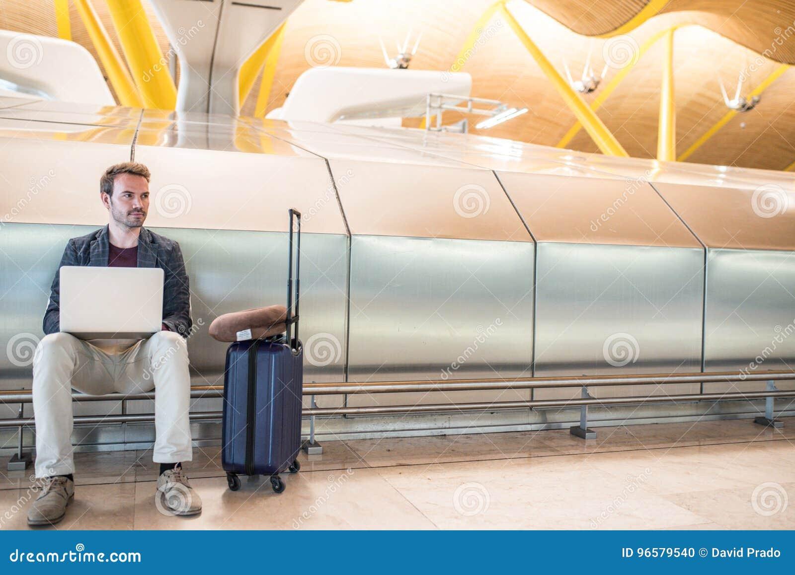 Jeune homme attirant s asseyant à l aéroport fonctionnant avec un lapto