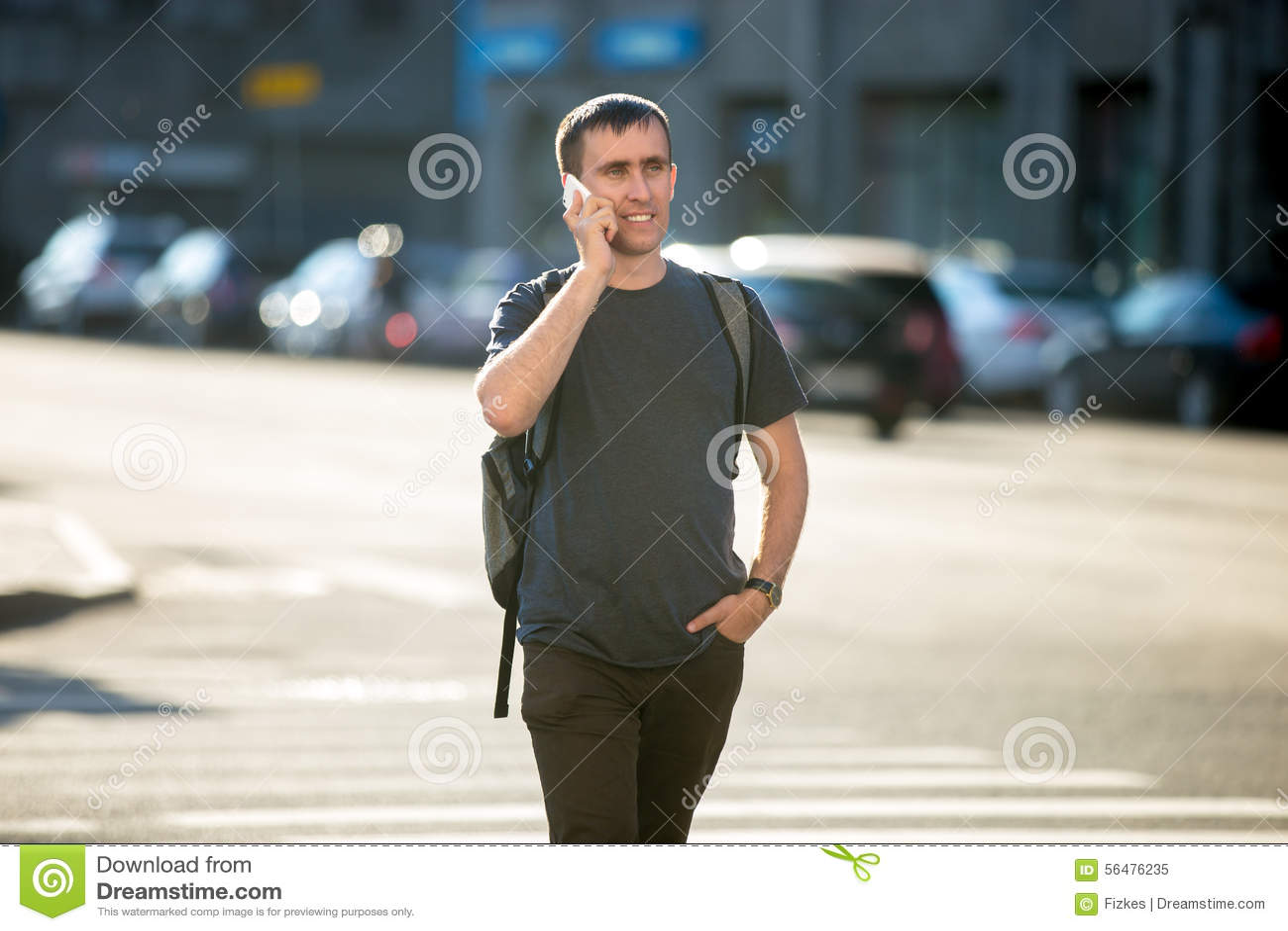 Jeune homme au téléphone sur le passage piéton piétonnier