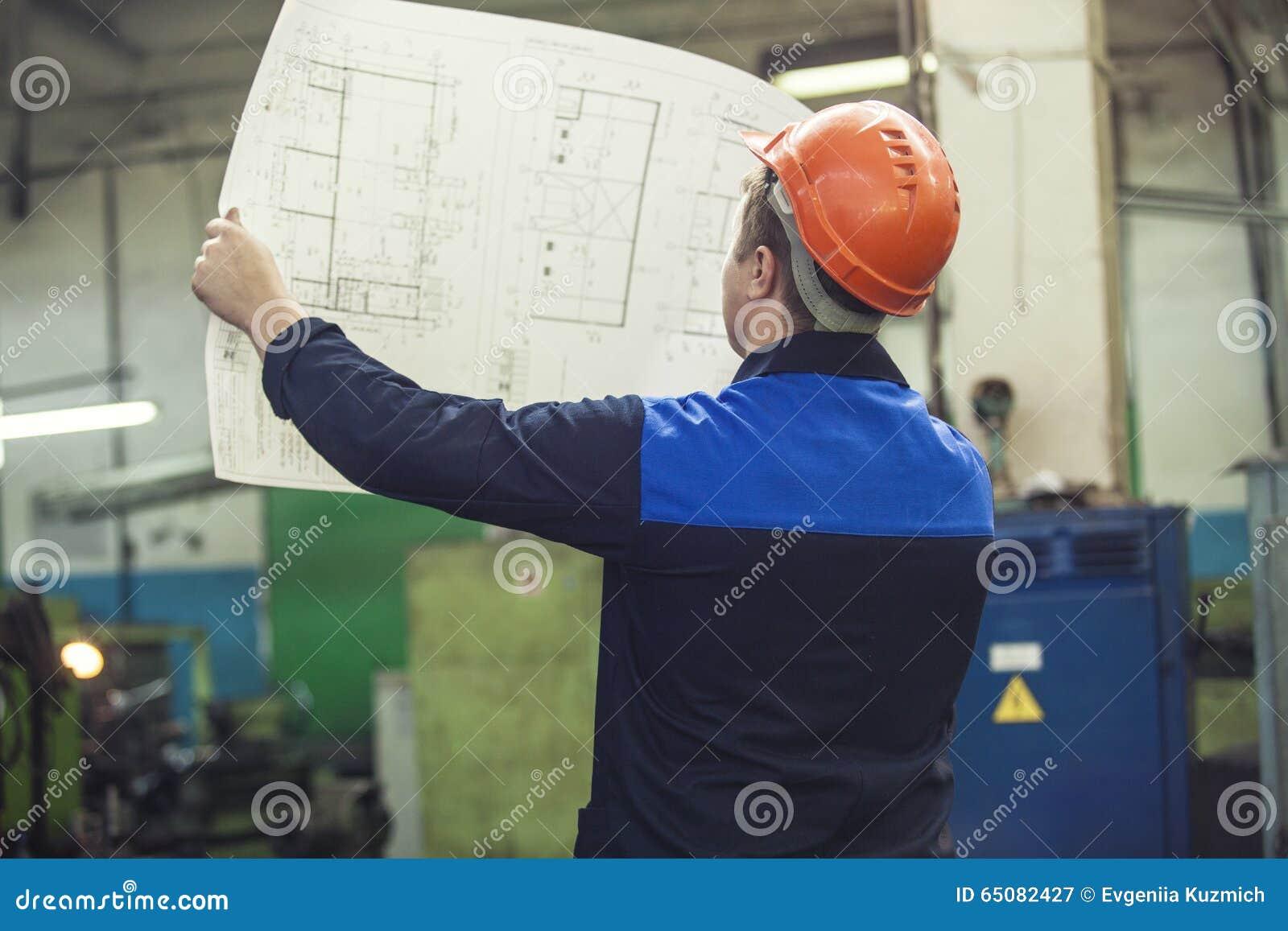Jeune homme avec des modèles travaillant à une vieille usine pour l inst