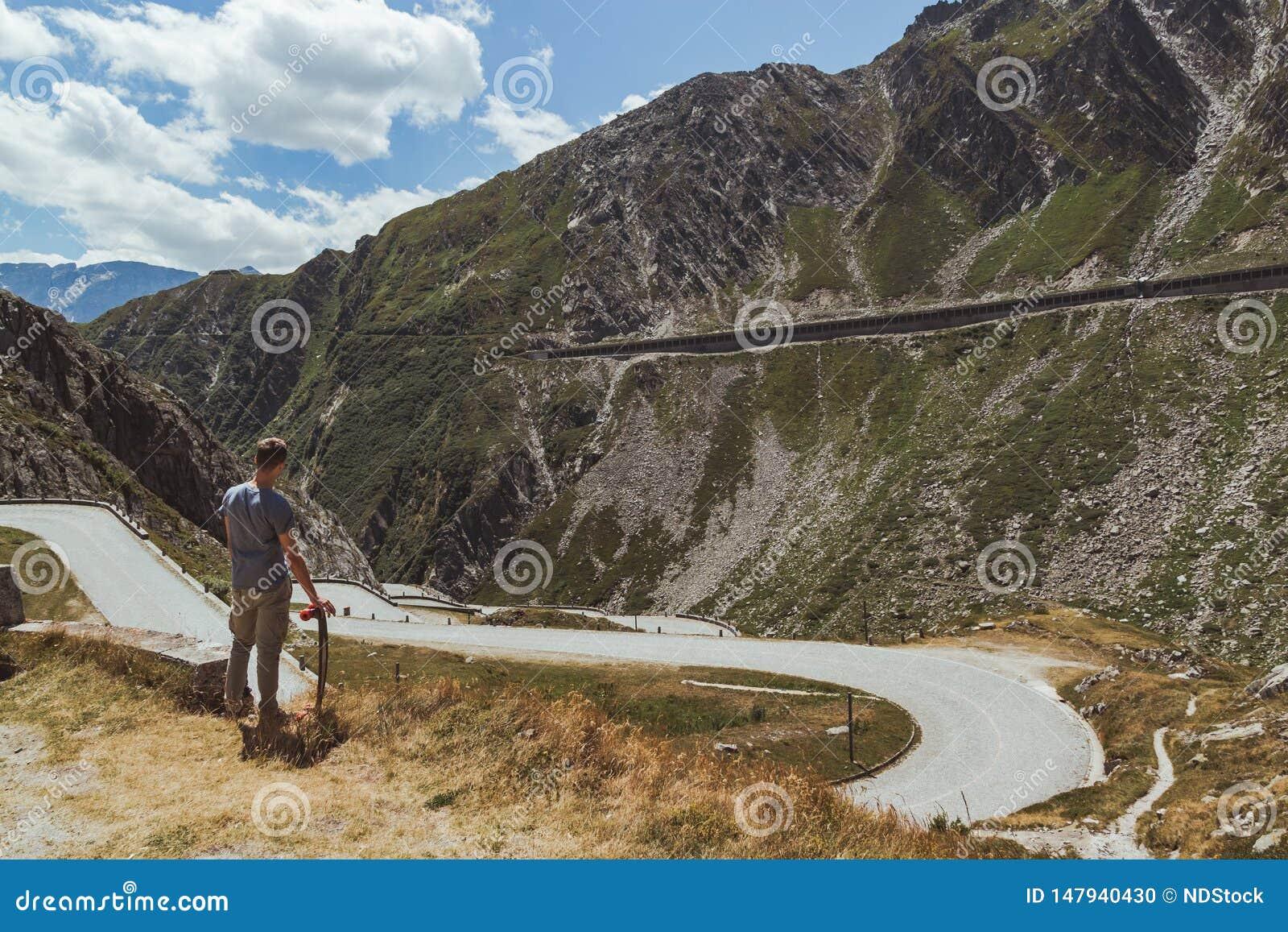 Jeune homme avec le longboard contemplant une route sinueuse descendant dans une vallée