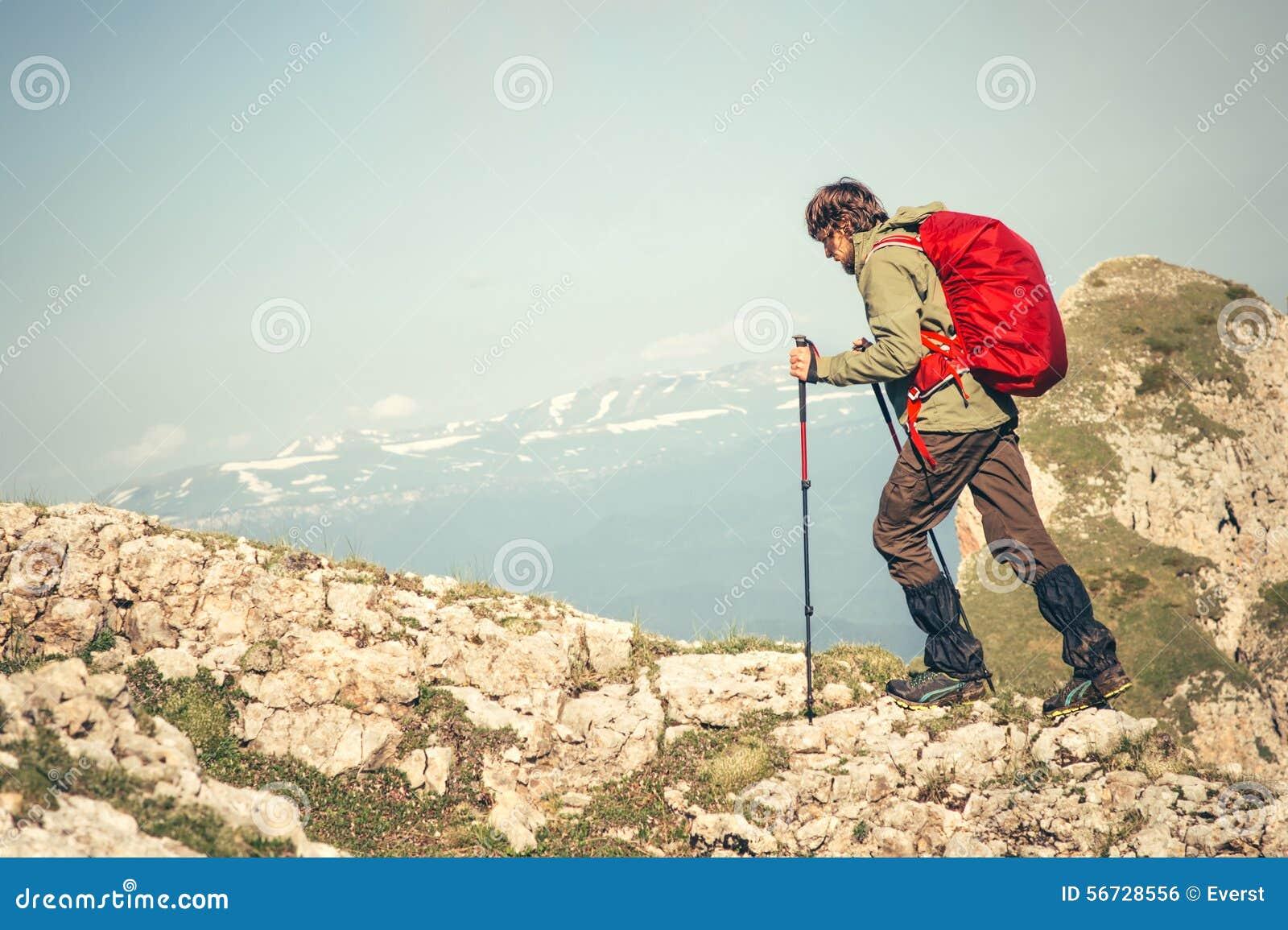 Jeune homme avec le sac à dos et fonctionnement de poteaux de trekking extérieur