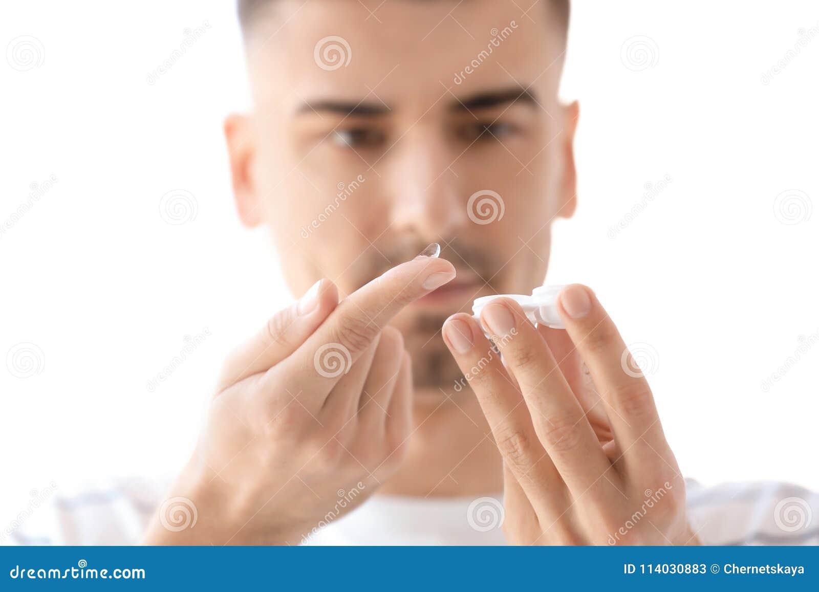 Jeune homme avec le verre de contact