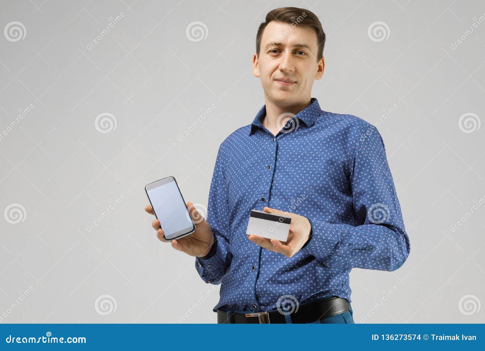Jeune homme avec une carte de banque et des supports de téléphone portable  d isolement sur c2de9add4db