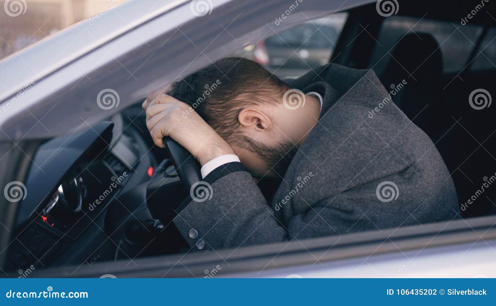 Jeune homme barbu d affaires s asseyant dans la voiture très bouleversée et soumise à une contrainte après échec dur et se déplaç