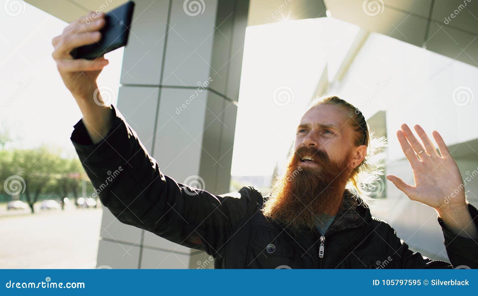Jeune homme barbu de hippie ayant la causerie visuelle en ligne avec l appareil-photo de smartphone tandis que rue de ville de vo