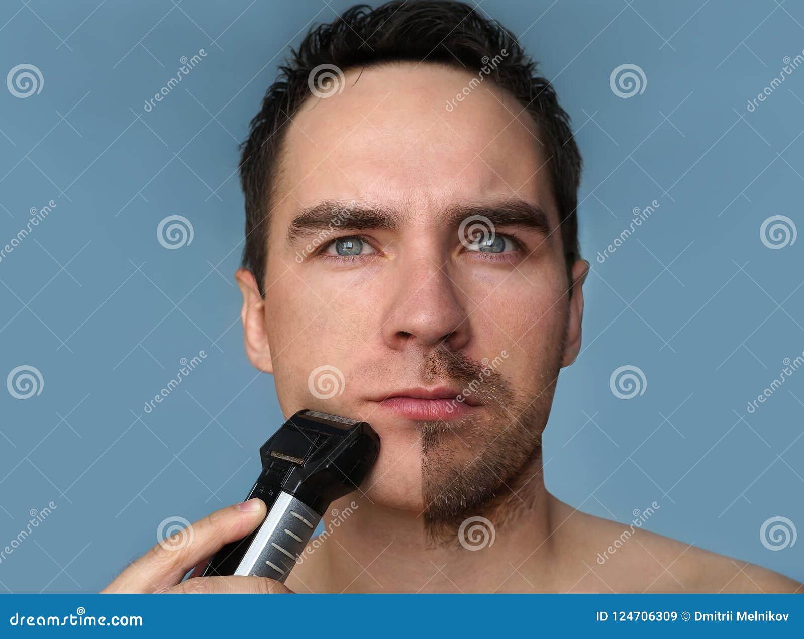 Jeune homme barbu pendant le toilettage de la barbe utilisant le trimmer Demi visage avec une moitié de barbe rasé