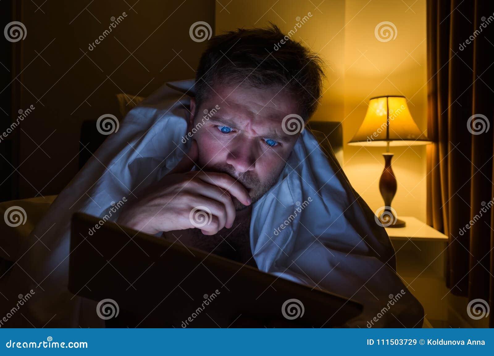 Jeune homme beau à la maison lisant avec la tablette se trouvant sur le lit la nuit Il est fatigué et veut dormir