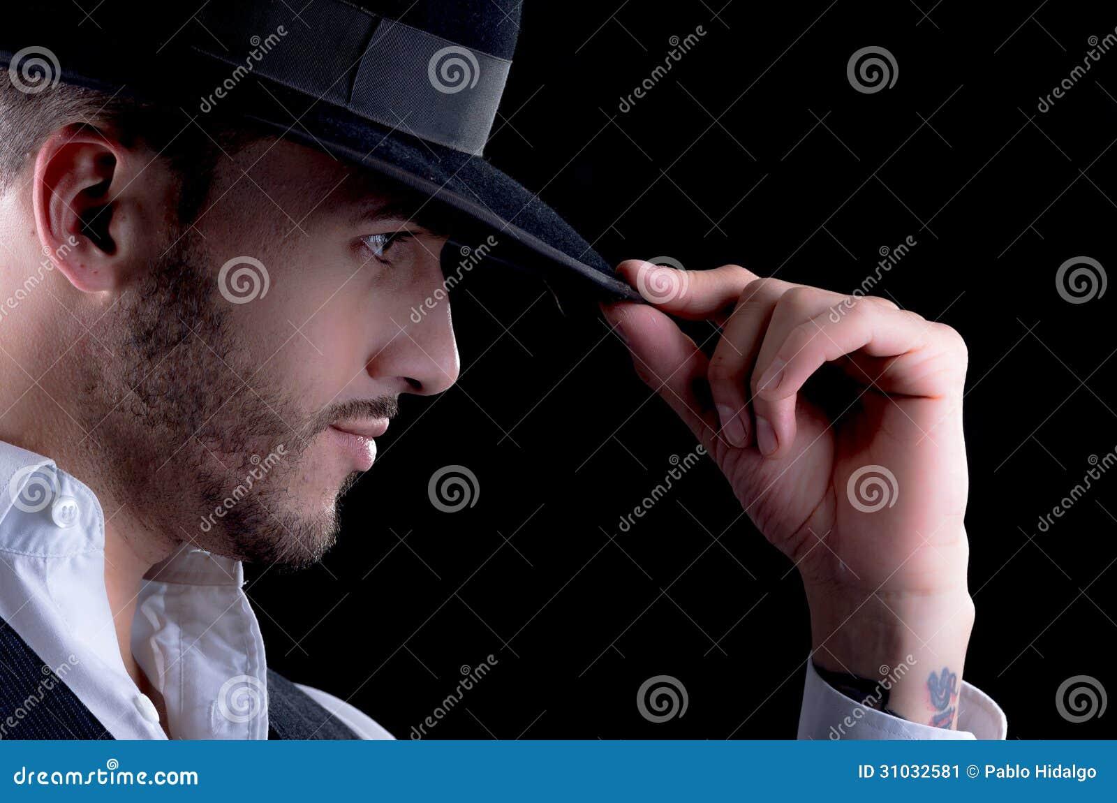 7637a8c620d91 Portrait de studio d'un jeune homme beau avec un chapeau à disposition sur  un fond noir