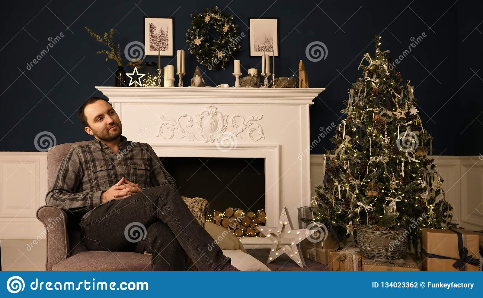 Jeune homme beau barbu de hippie dans roomthinking de Noël des idées de cadeau rêverie