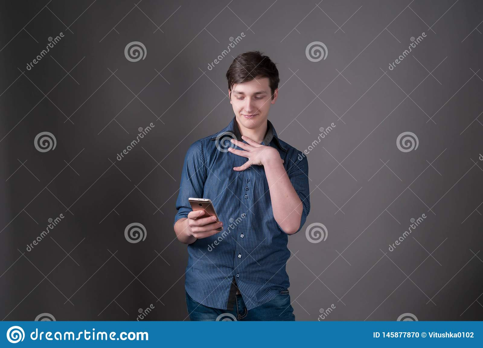 Jeune homme beau confus dans la chemise bleue souriant et regardant le smartphone sur le fond gris