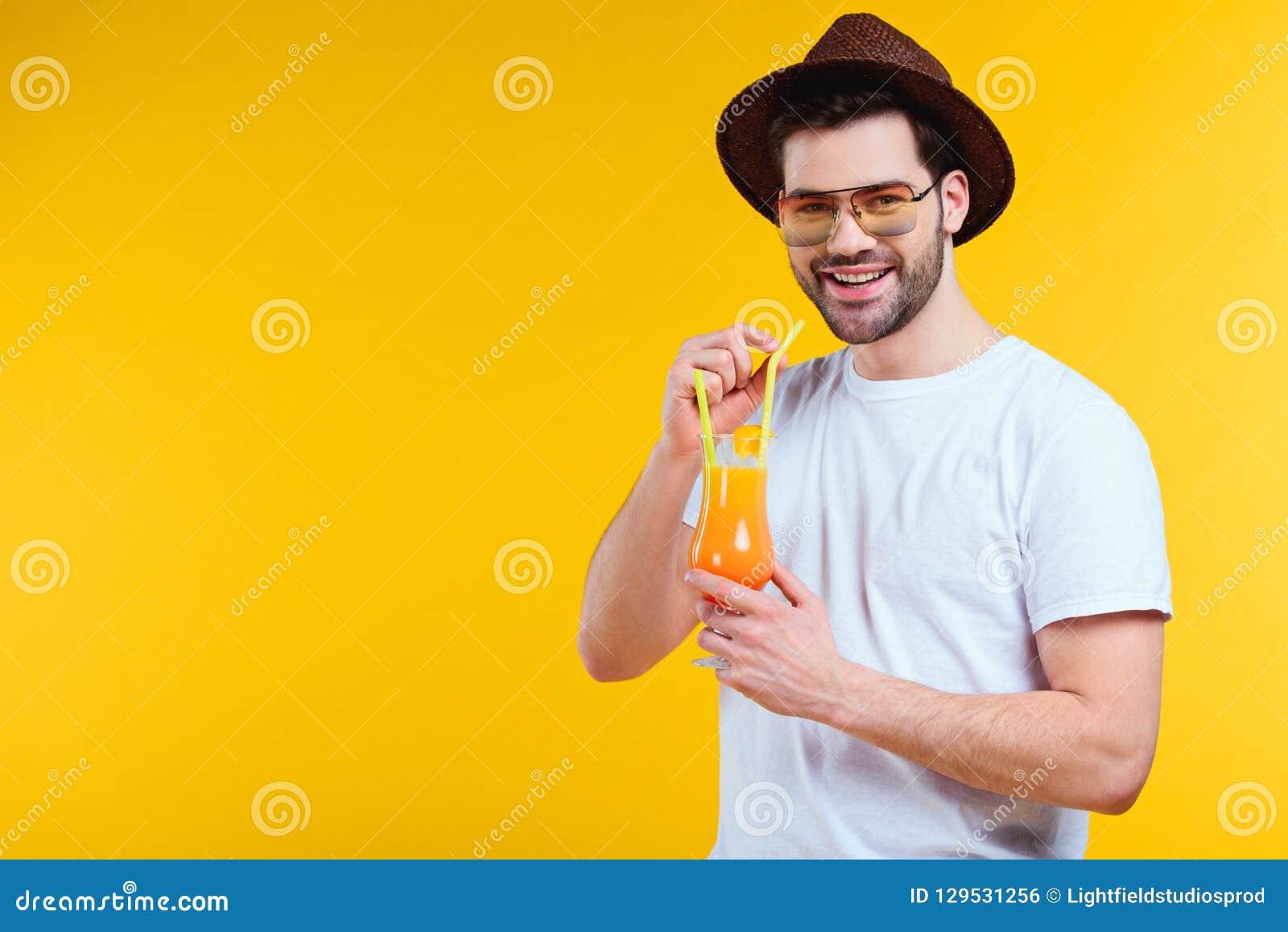 Jeune homme beau dans le chapeau et des lunettes de soleil buvant le cocktail d été et souriant à la caméra