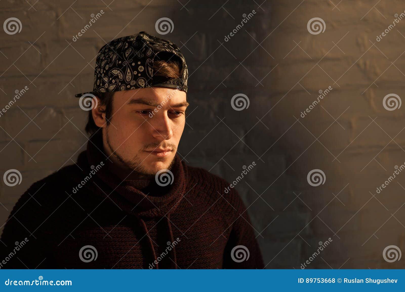 Jeune homme beau dans une casquette de baseball sur le fond de mur de briques