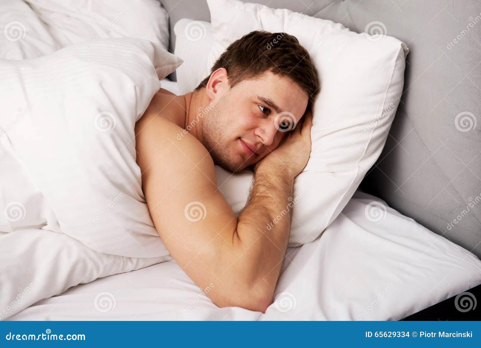 Jeune homme beau se situant dans le lit