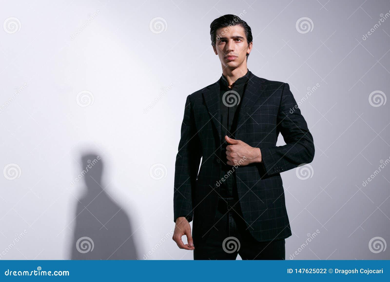 Jeune homme bel à la mode dans un costume élégant, tenant la main sur la veste de contrôleurs, d isolement sur le fond blanc