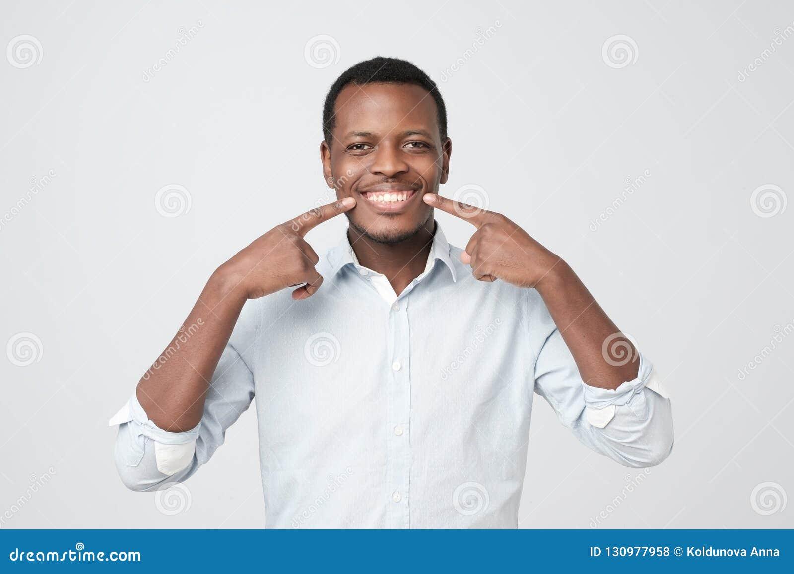 Jeune homme bel africain montrant ses excellentes dents blanches