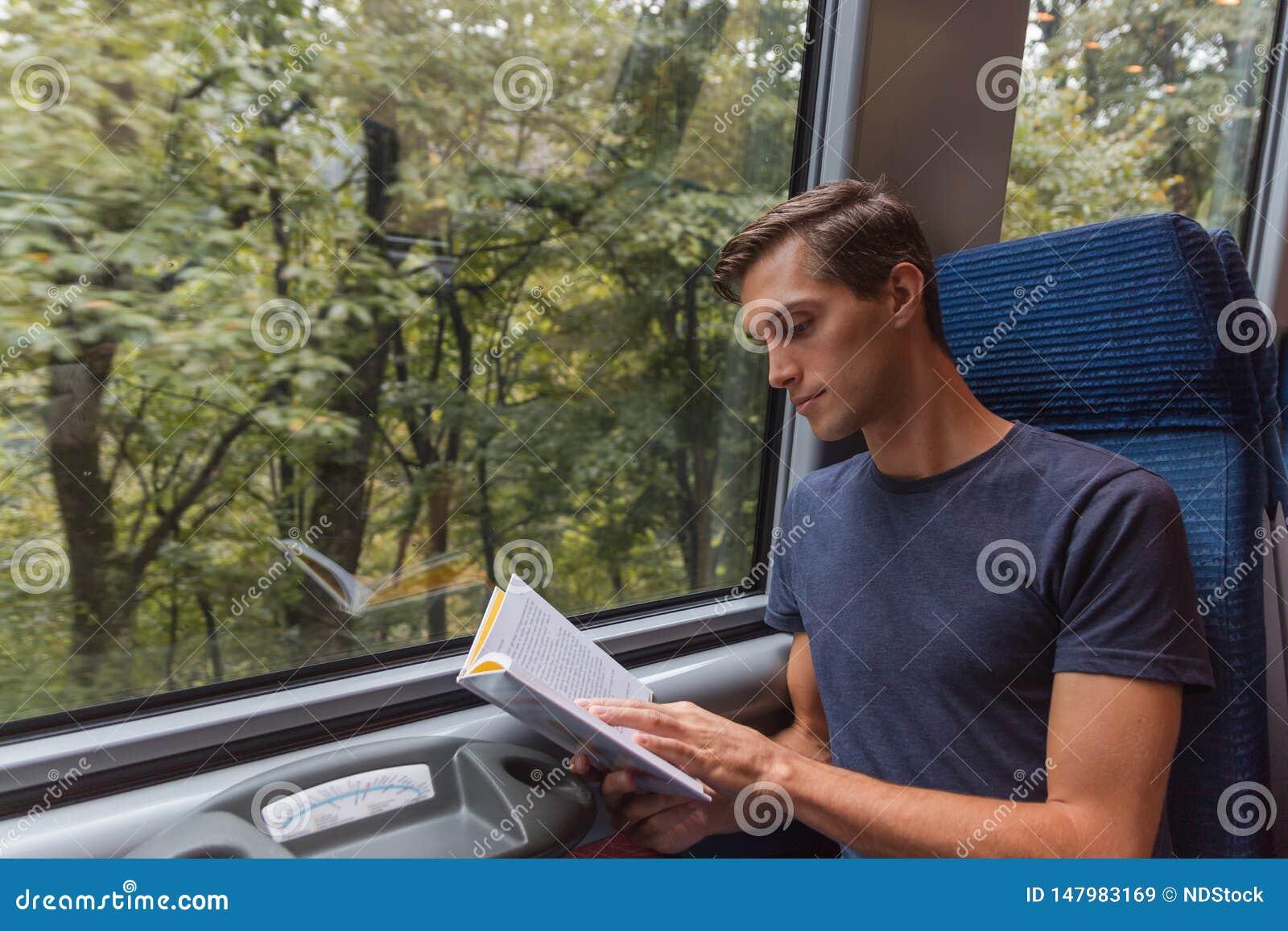 Jeune homme bel lisant un livre tout en voyageant par chemin de fer