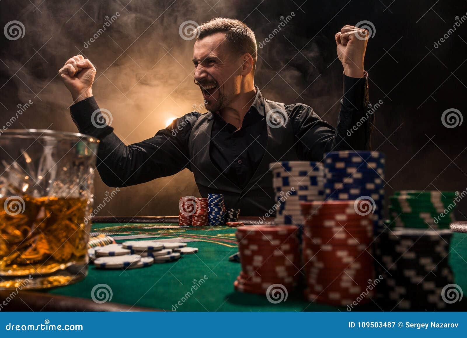 Jeune homme bel s asseyant derrière la table de tisonnier avec des cartes et des puces
