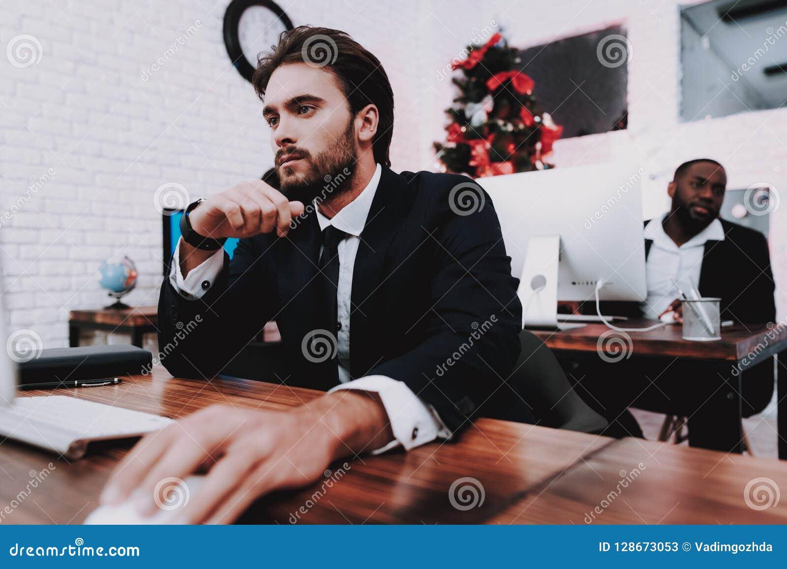 Jeune homme bouleversé travaillant dans le bureau la soirée du Nouveau an
