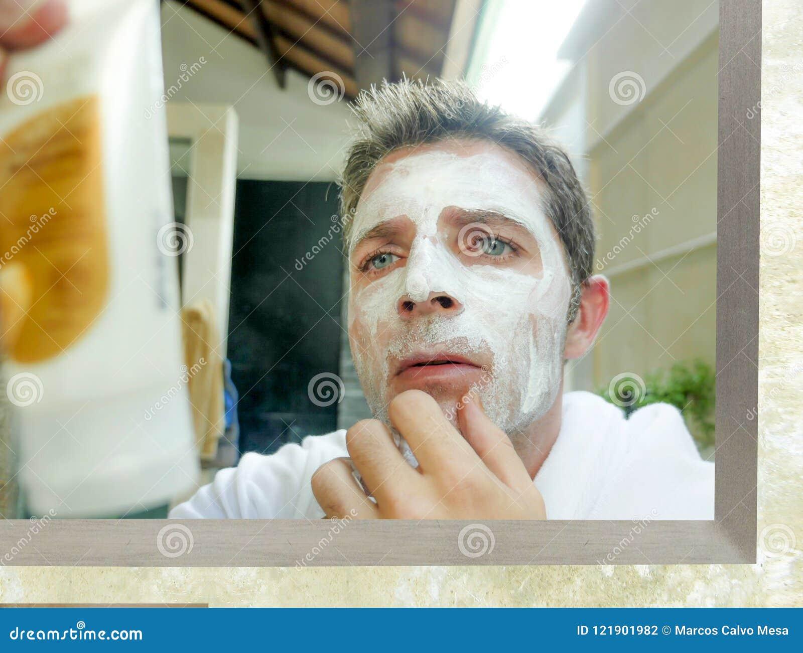 Jeune homme caucasien confus à la maison lisant des instructions du produit blanc de facemask tout en appliquant le masque facial