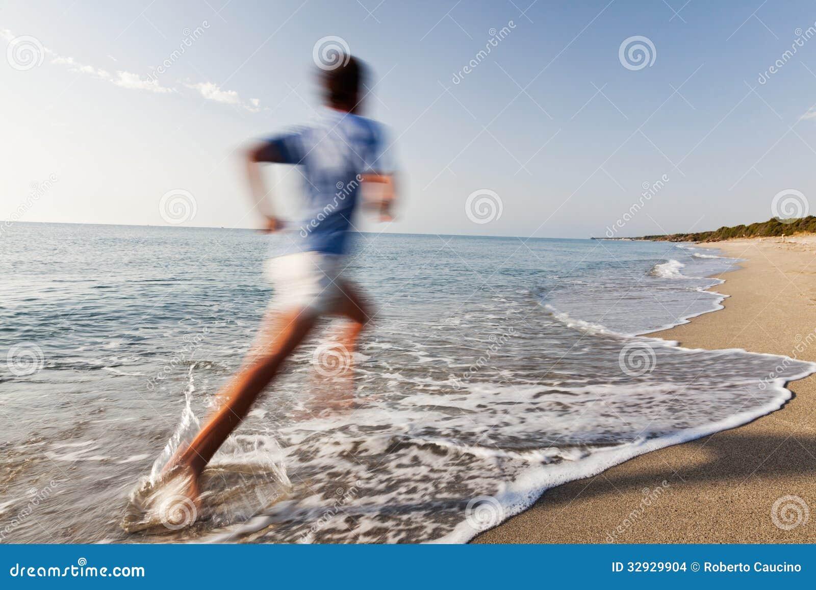 Jeune homme courant sur une plage.