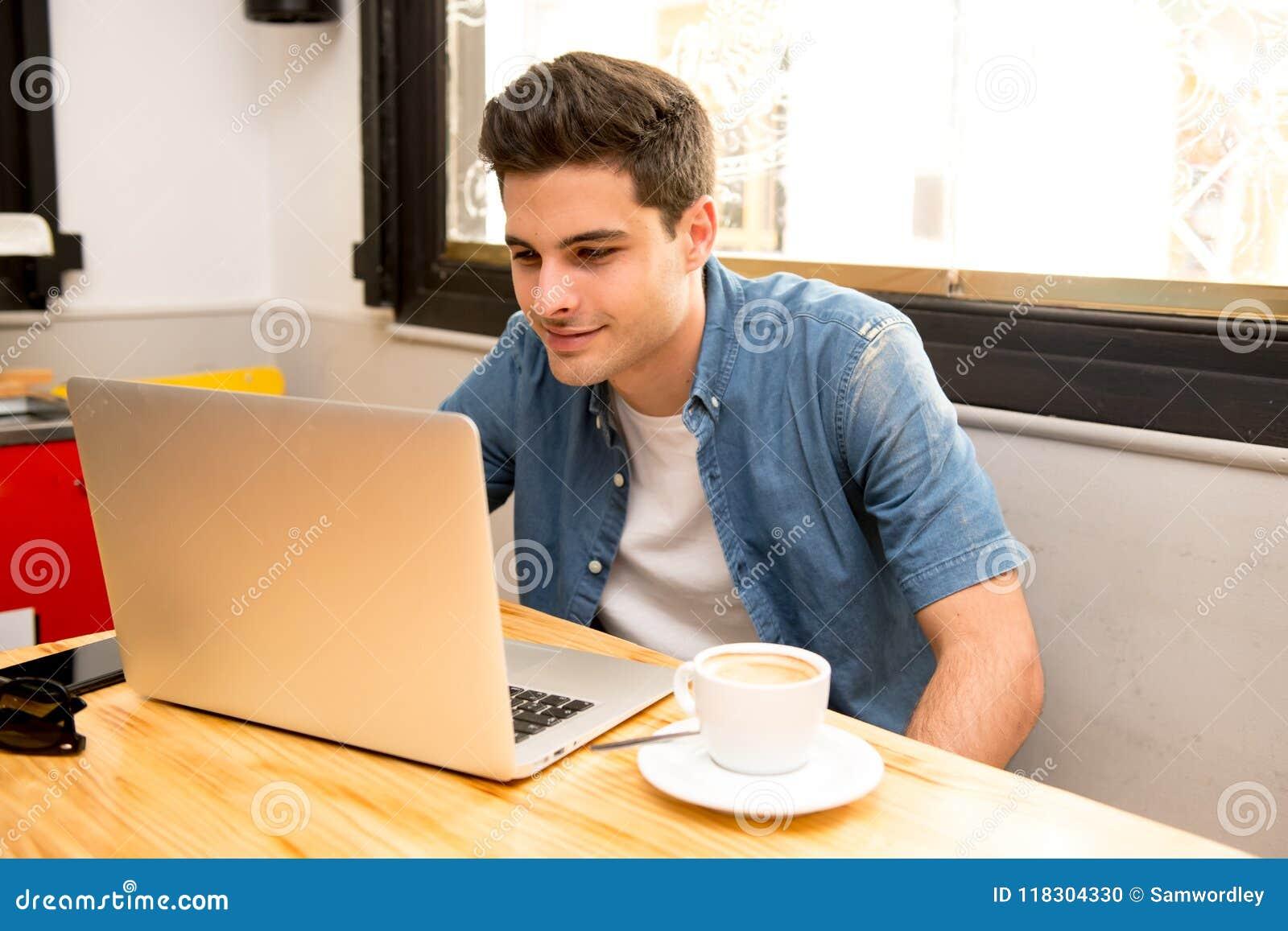 Jeune homme d étudiant travaillant et étudiant sur l ordinateur dans le café