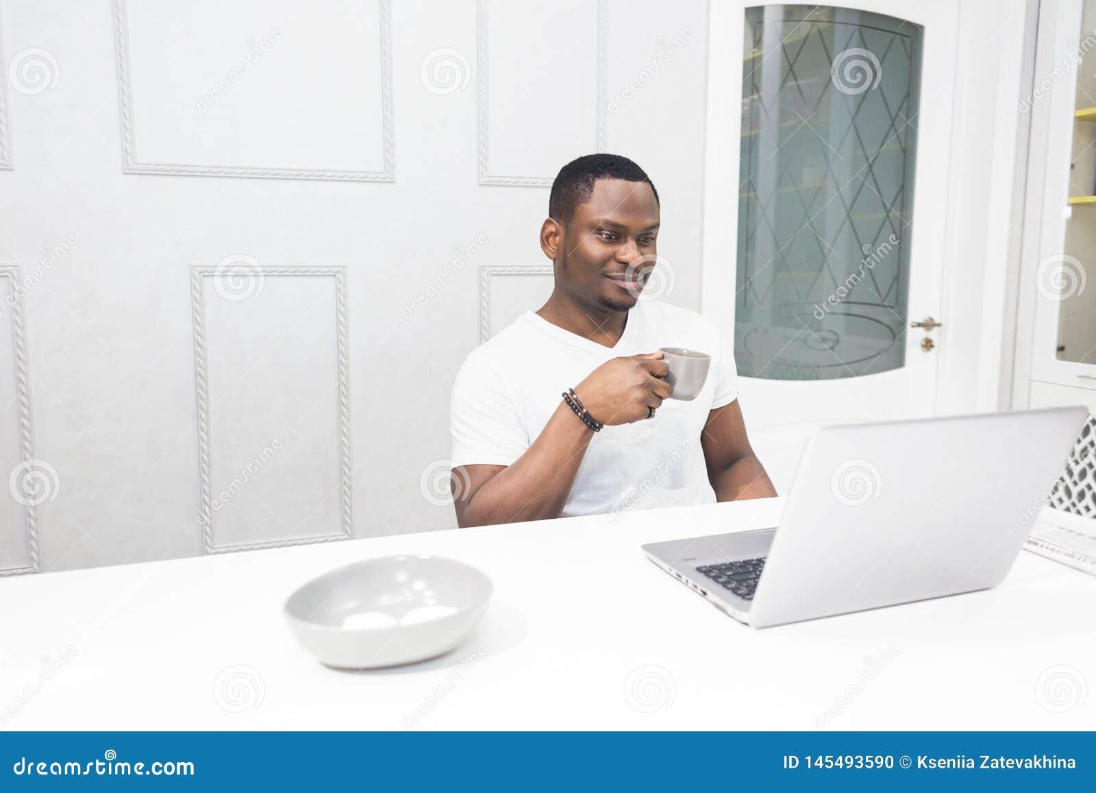 Jeune homme d affaires d Afro-am?ricain travaillant sur un ordinateur portable dans la cuisine dans un int?rieur moderne