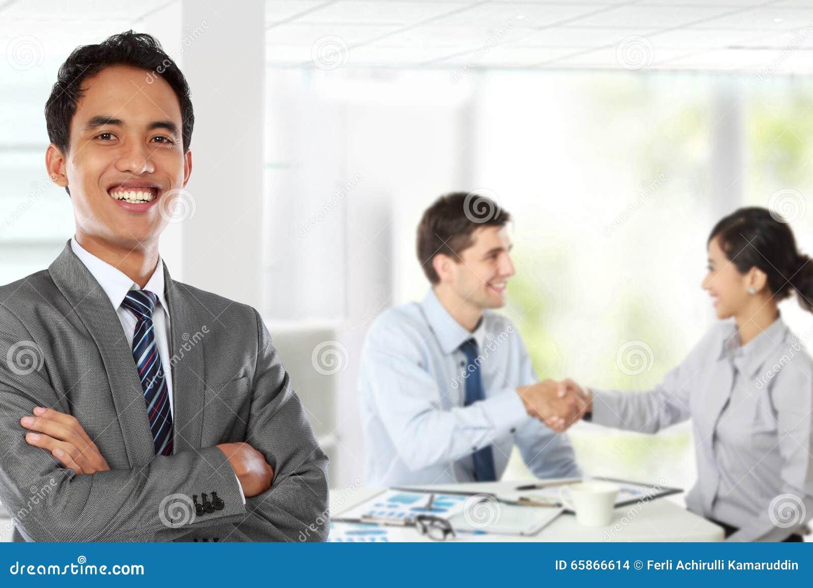 Jeune homme d affaires asiatique, avec son équipe derrière
