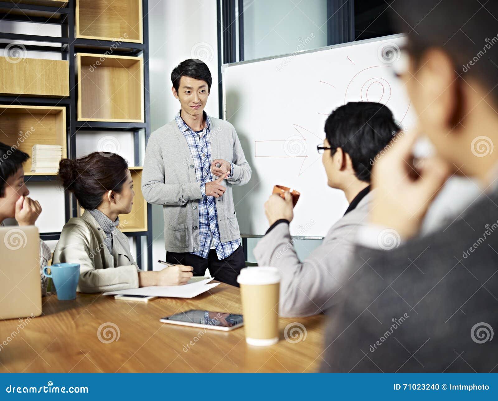 Jeune homme d affaires asiatique facilitant une discussion