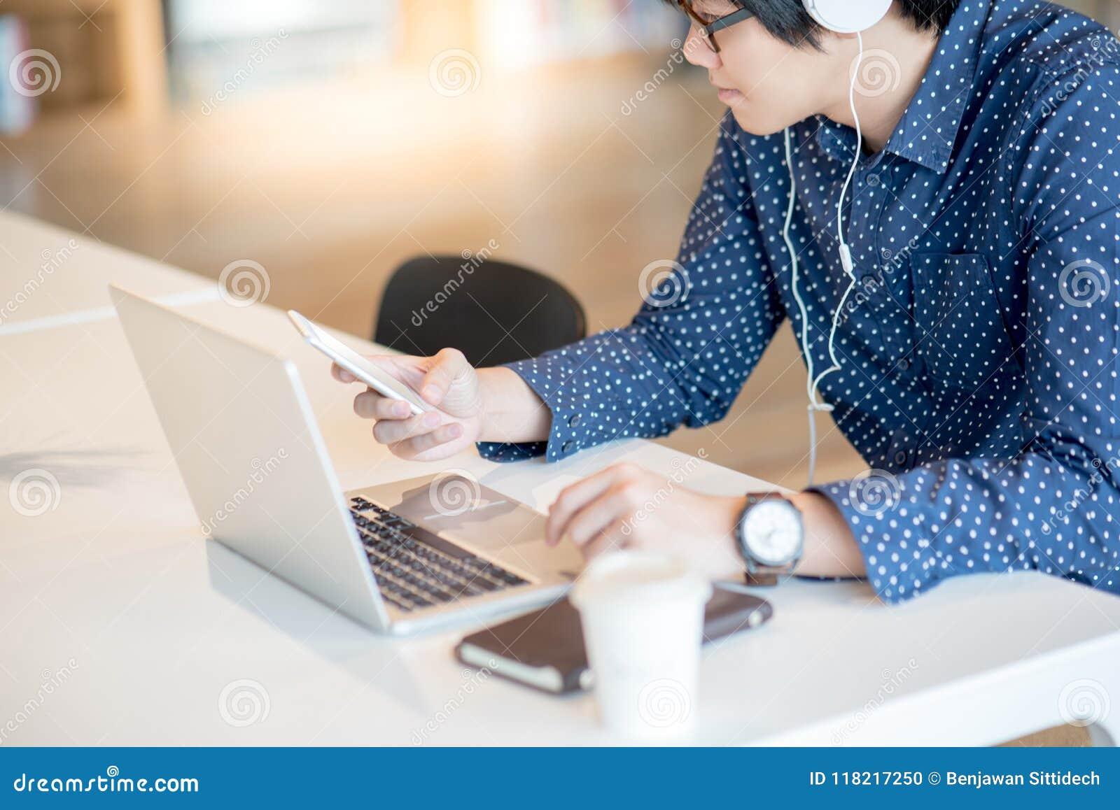 Jeune homme d affaires asiatique utilisant le smartphone fonctionnant avec l ordinateur portable
