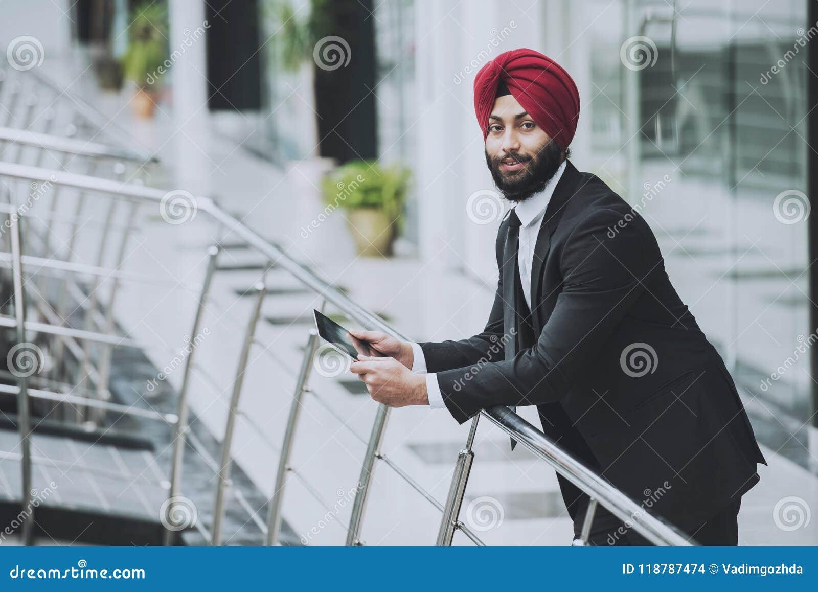 Jeune homme d affaires barbu indien dans le bureau moderne