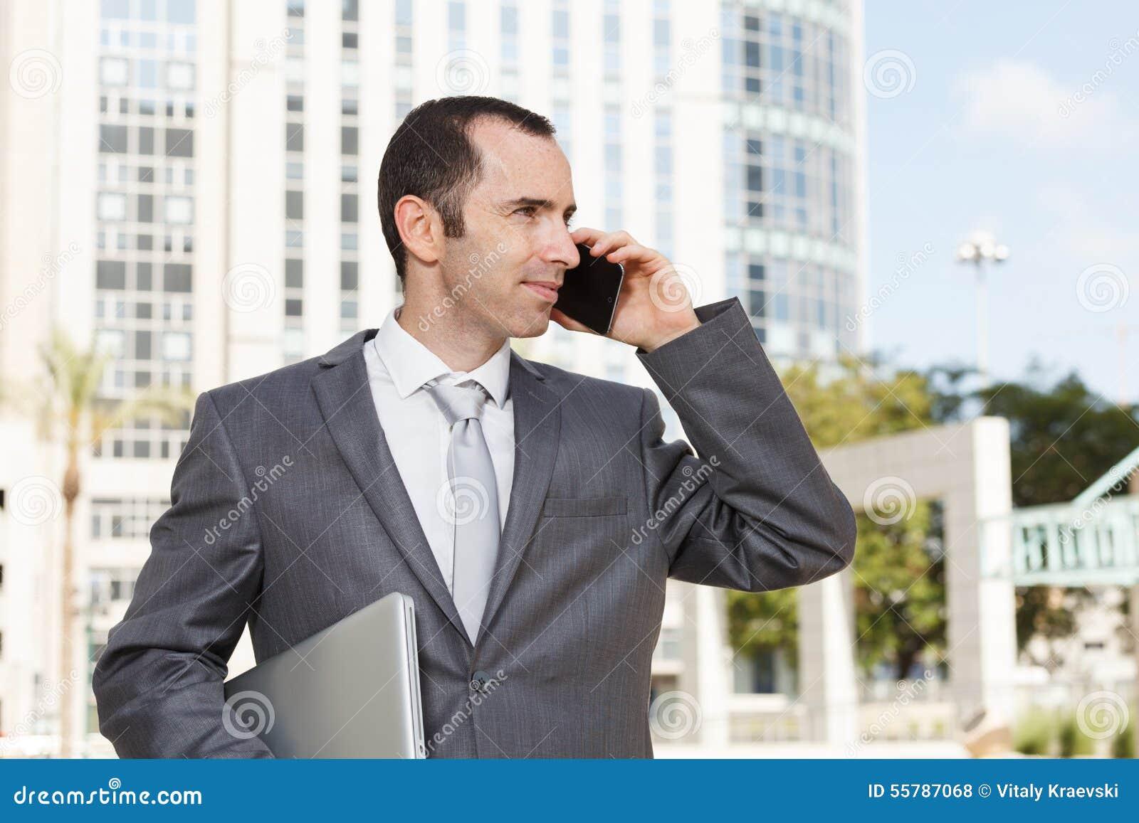 Jeune homme d affaires beau utilisant le téléphone portable devant moderne