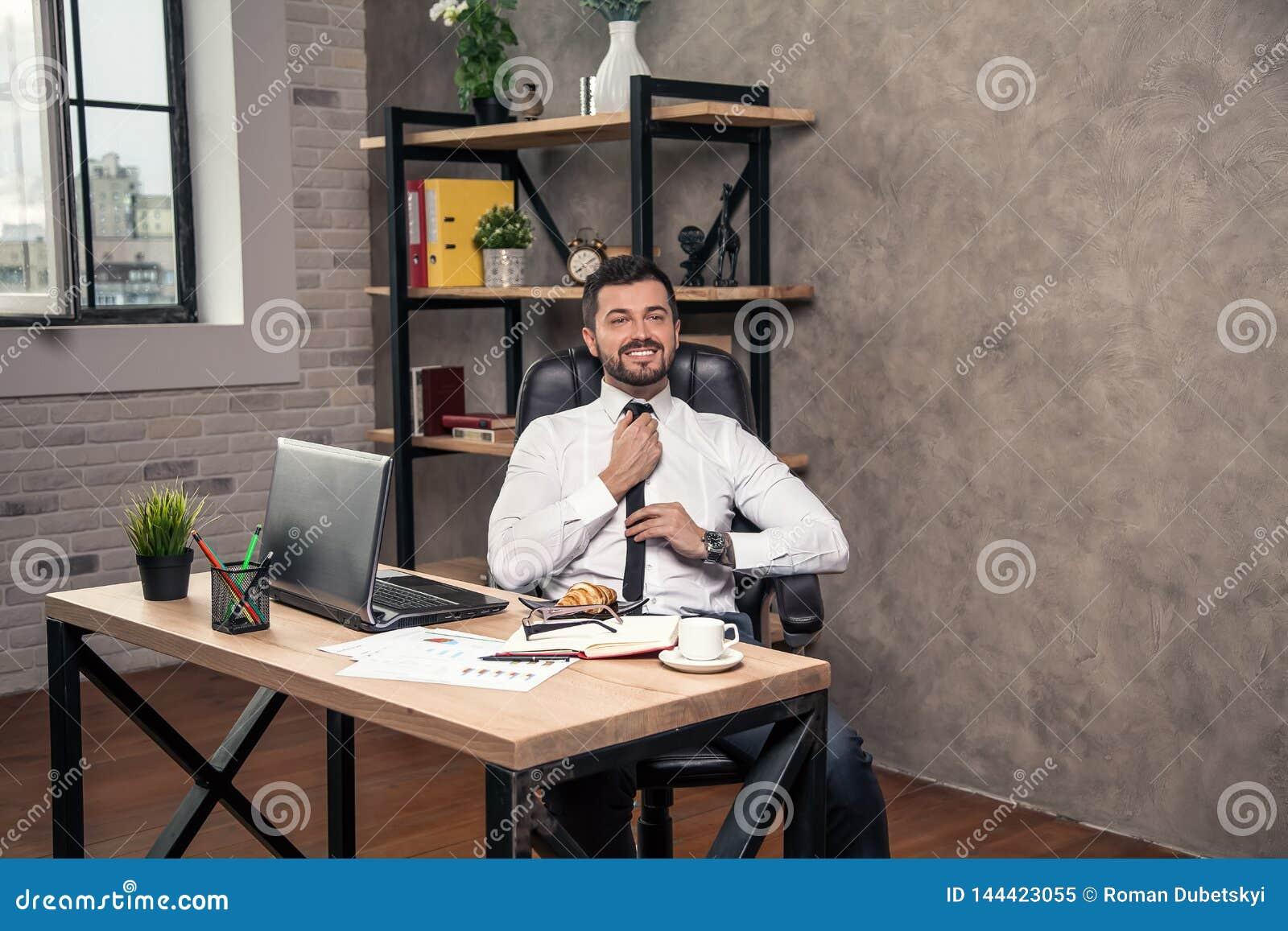 Jeune homme d affaires bel élégant travaillant à son bureau dans le bureau fixant son lien et sourire
