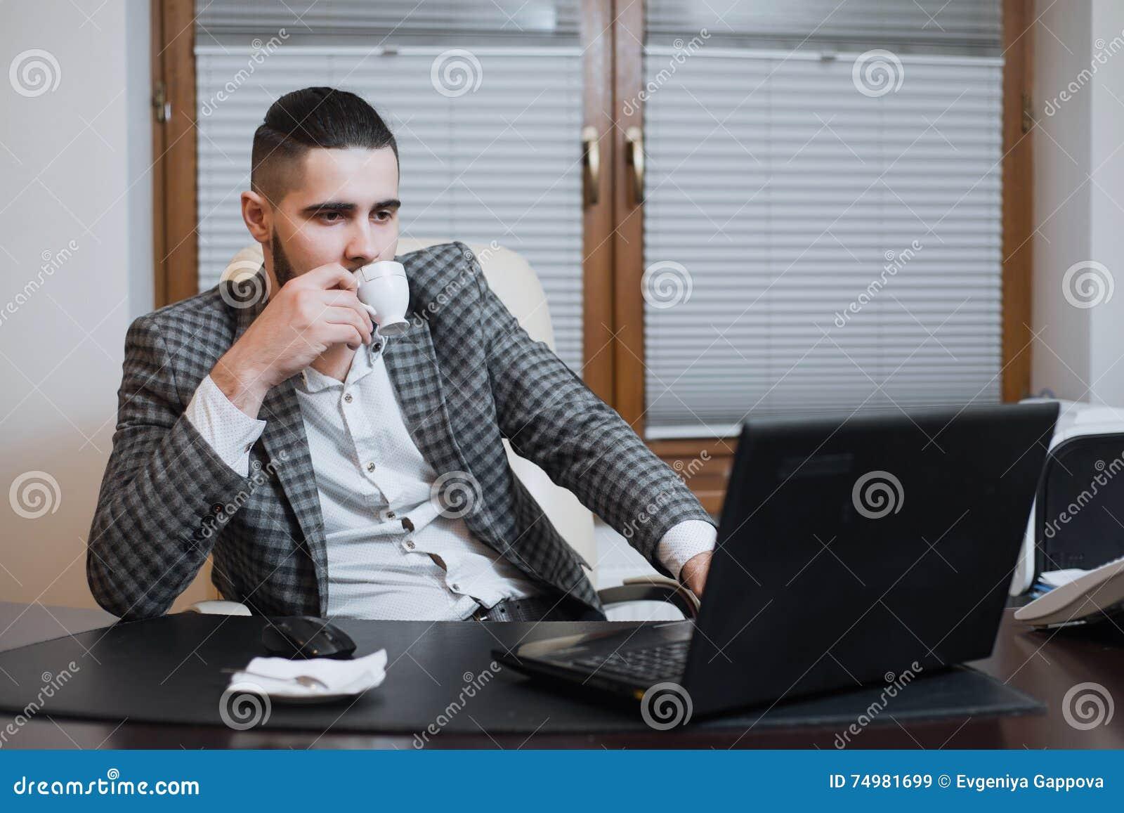 Jeune homme d affaires bel travaillant sur l ordinateur portable pendant la pause-café au bureau