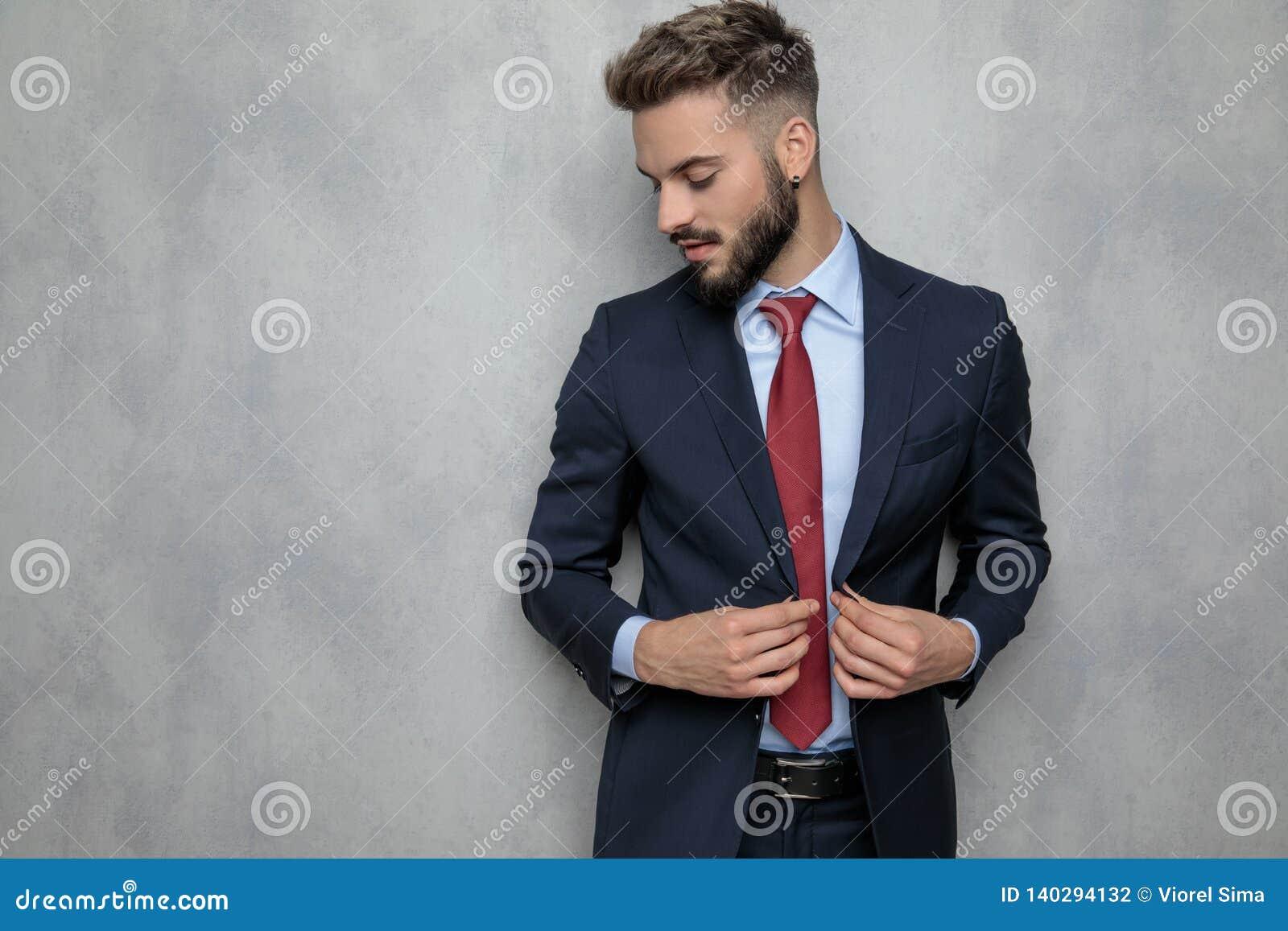 Jeune homme d affaires déboutonnant ses sourires et regards de manteau vers le bas