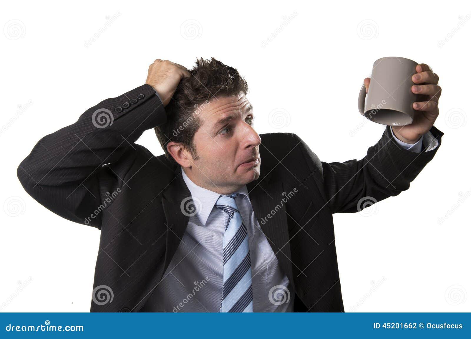 Jeune homme d affaires d intoxiqué dans le costume et lien jugeant la tasse de café vide soucieuse