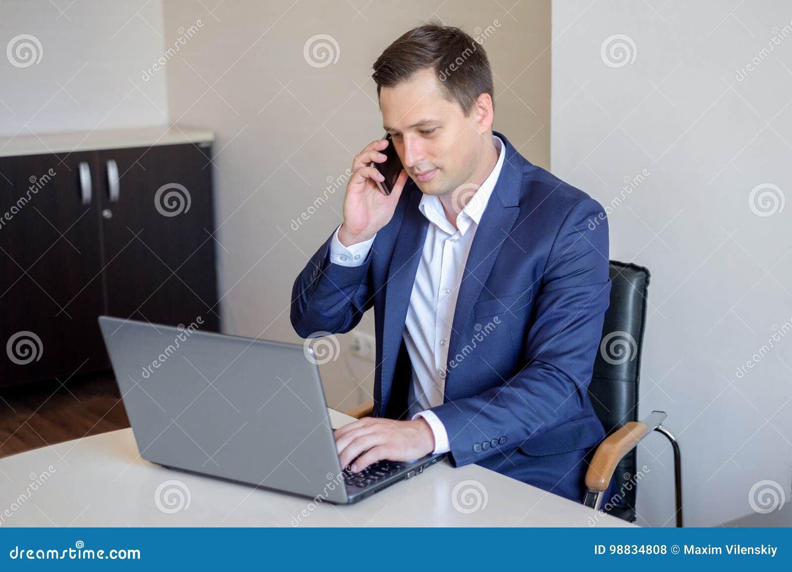 Jeune homme d affaires de sourire s asseyant derrière son bureau avec l ordinateur portable et parlant au téléphone portable dans