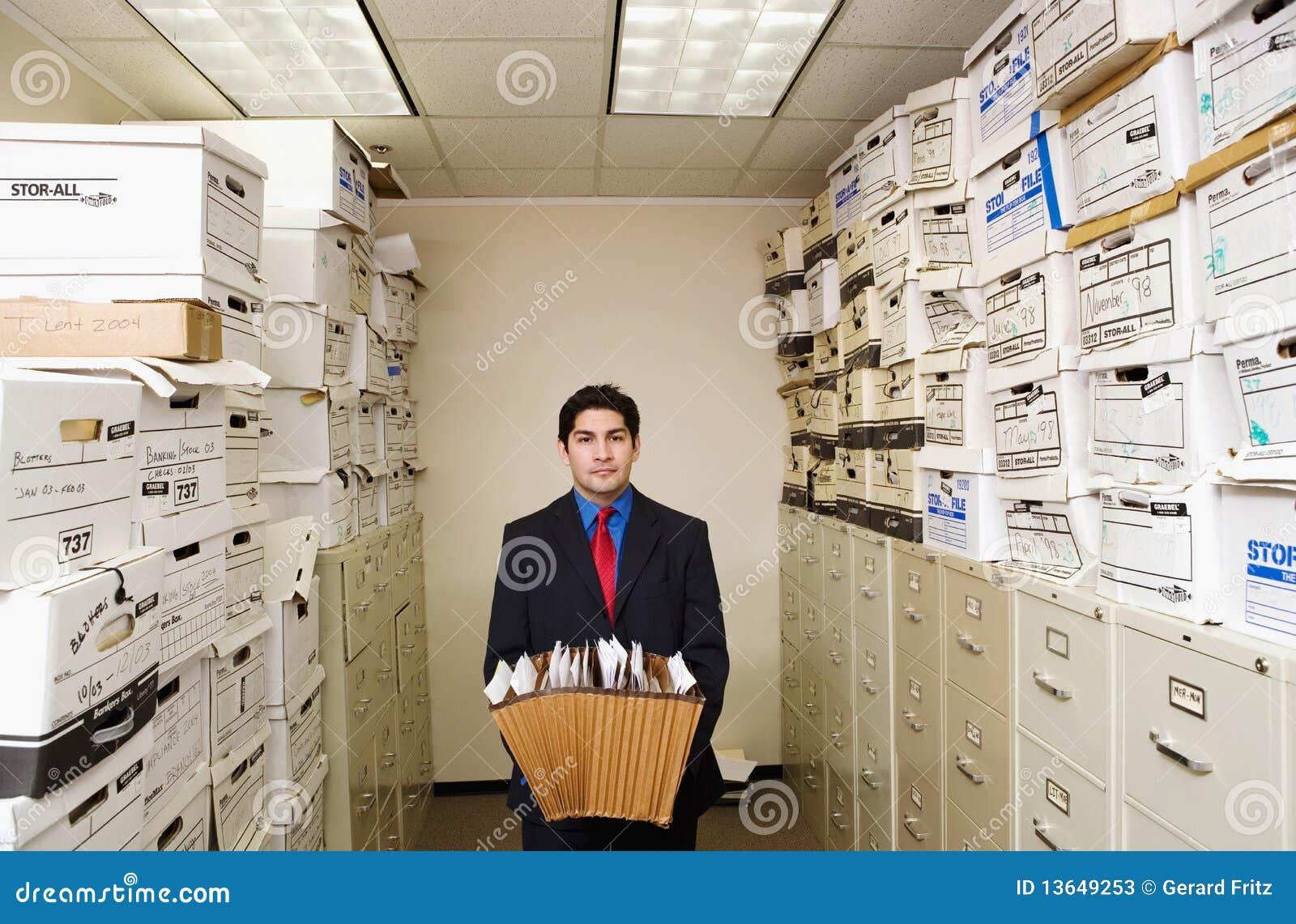 Jeune homme d affaires parmi des fichiers