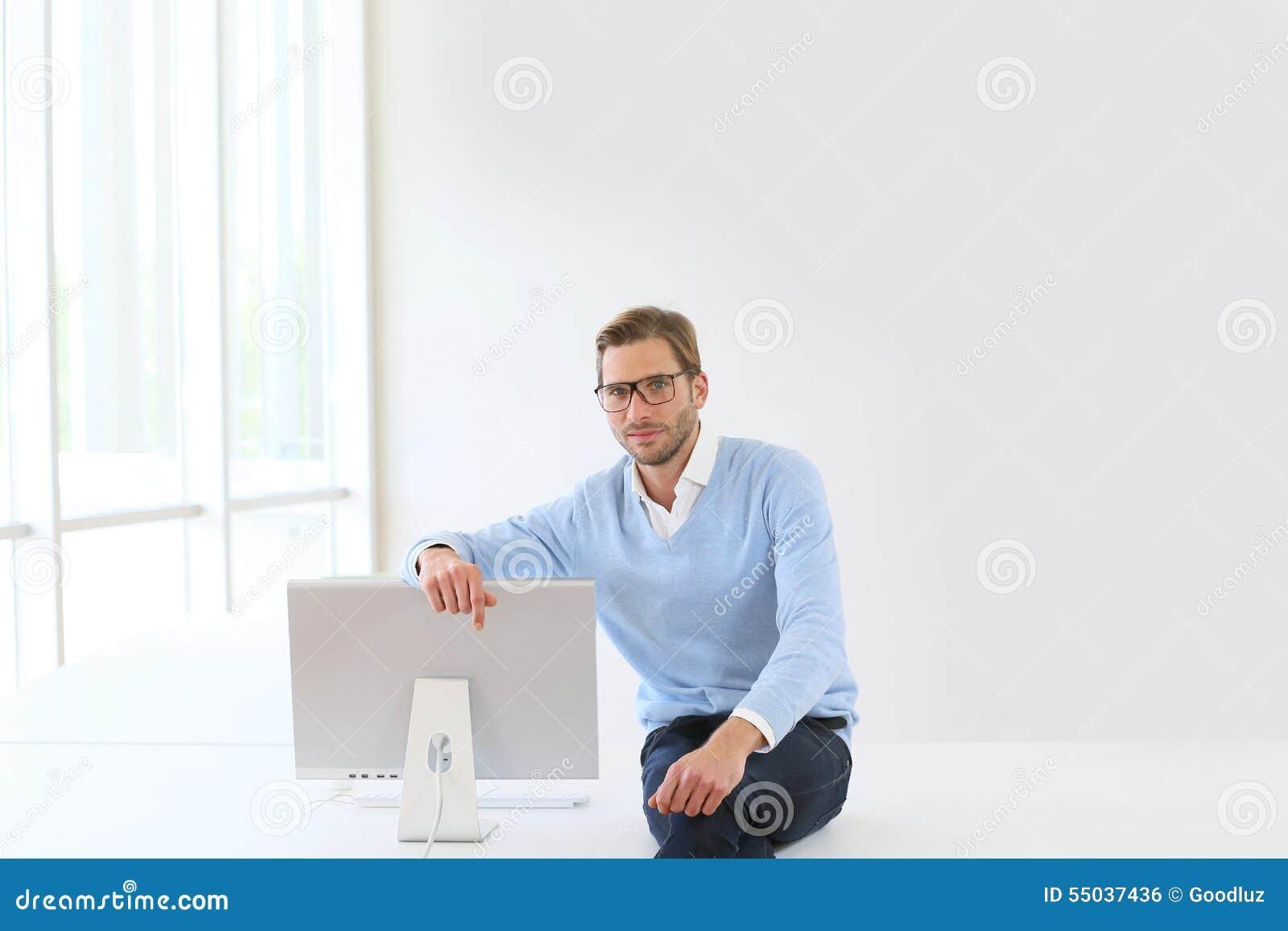 Jeune homme d affaires s asseyant près de l ordinateur
