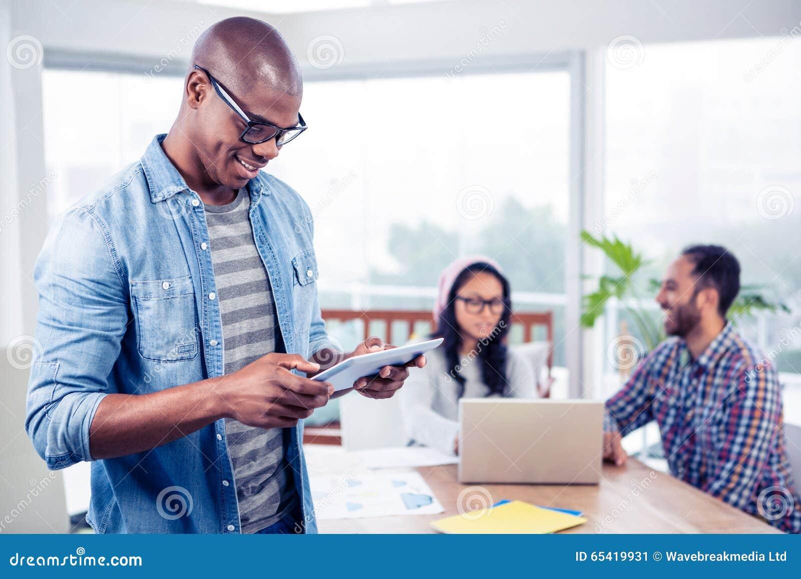 Jeune homme d affaires utilisant le comprimé numérique tout en se tenant dans le bureau
