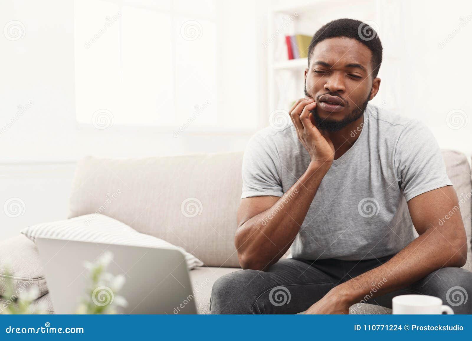 Jeune homme d afro-américain ayant le mal de dents à la maison