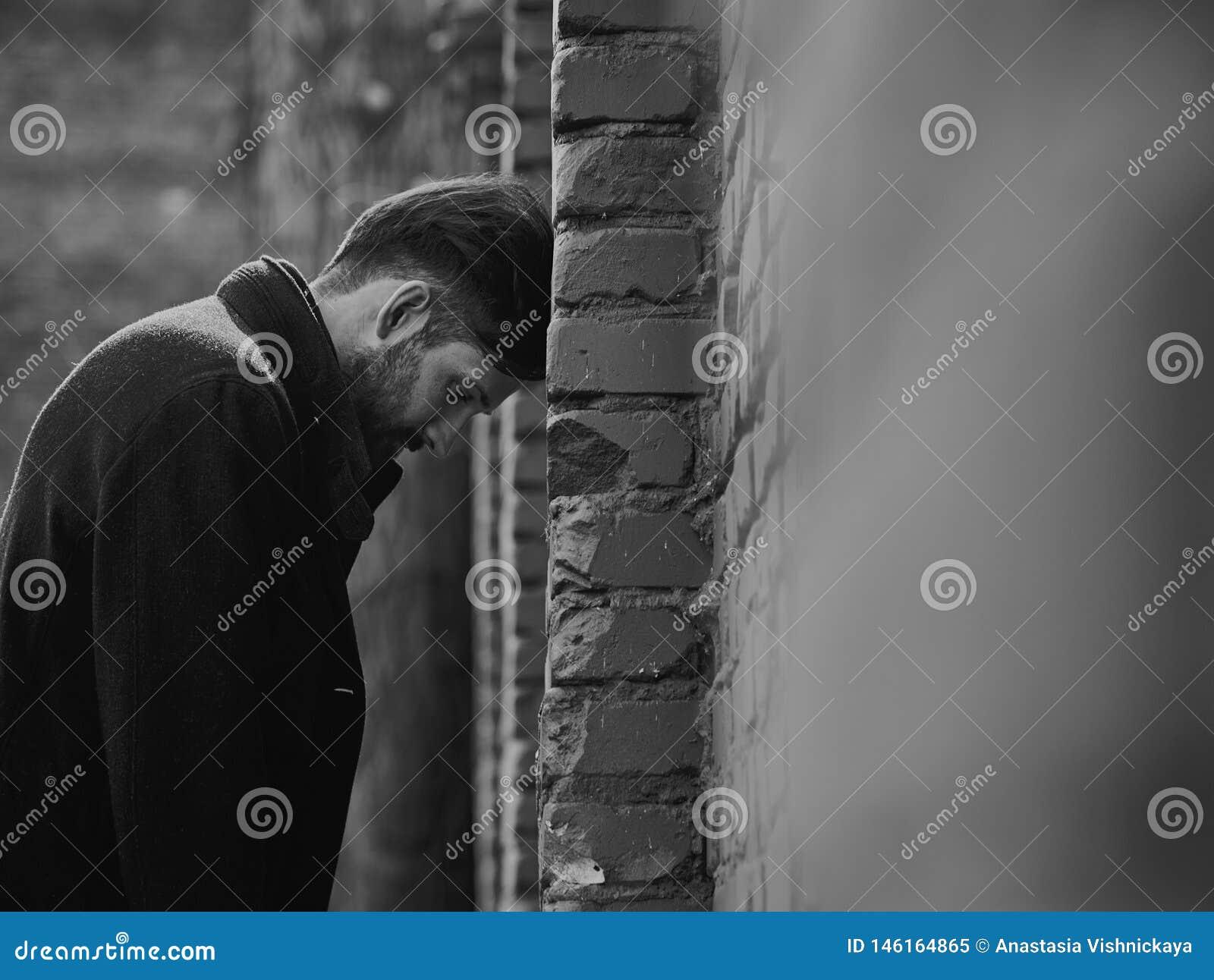 Jeune homme d?prim? frustrant pr?s du mur de briques semblant f?ch? Portrait dramatique modifié la tonalité triste de plan rappro
