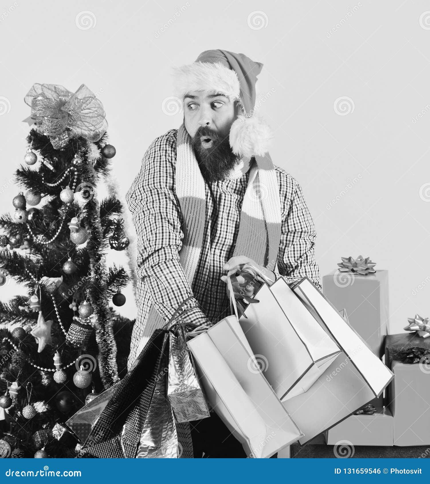 Jeune homme dans le chapeau de Santa marchant avec des sacs à provisions