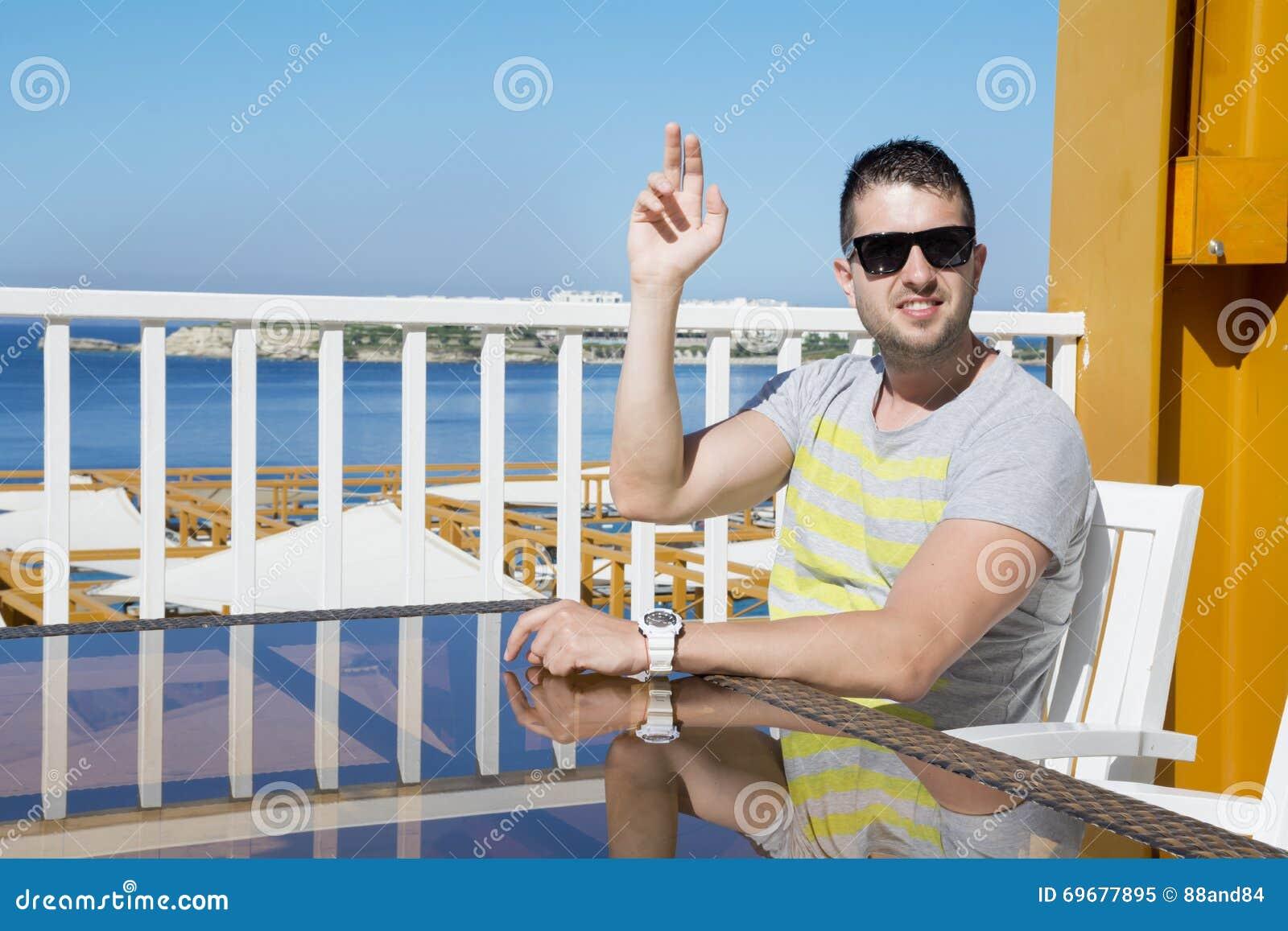 Jeune homme dans le restaurant de mer appelle le serveur