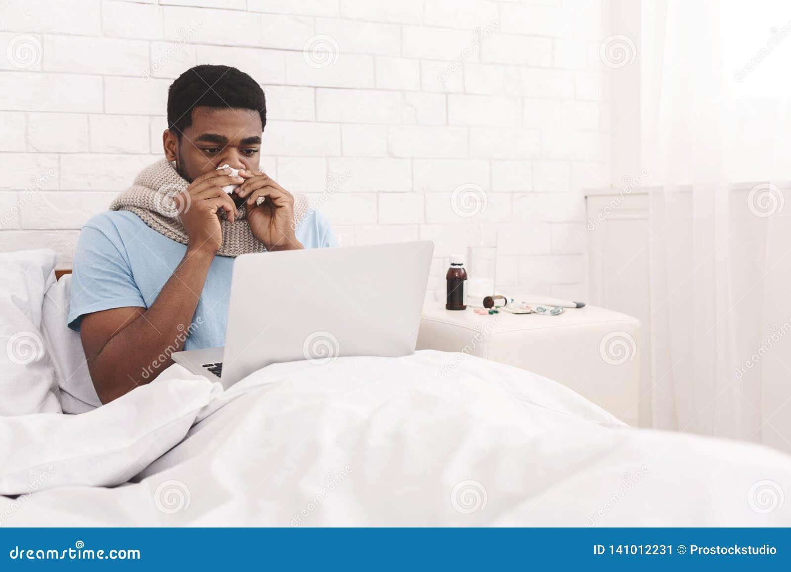 Lit Pour Jeune Homme jeune homme de couleur malade travaillant sur l'ordinateur