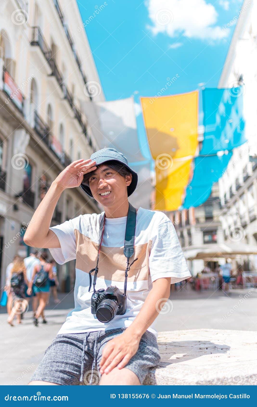 Jeune homme de touristes asiatique s asseyant dehors avec une caméra