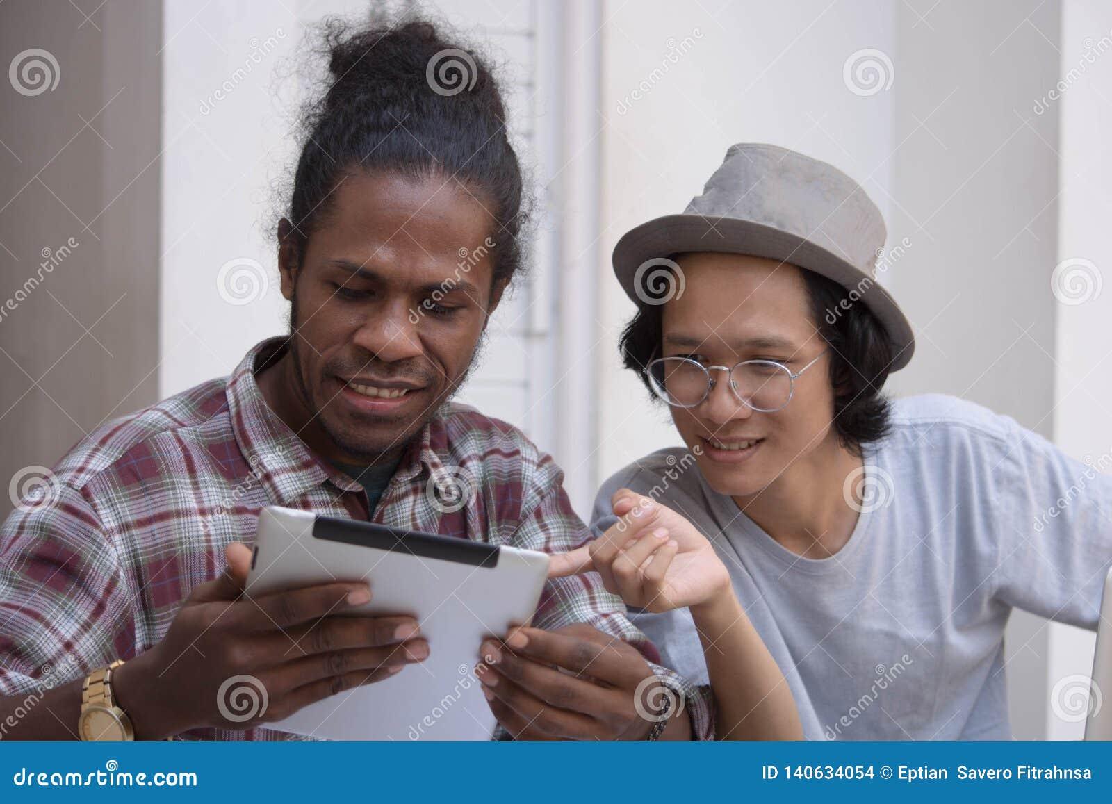 Jeune homme deux créatif discuter avec l ordinateur portable et le comprimé, le jeune Asiatique et l homme de couleur travaillant