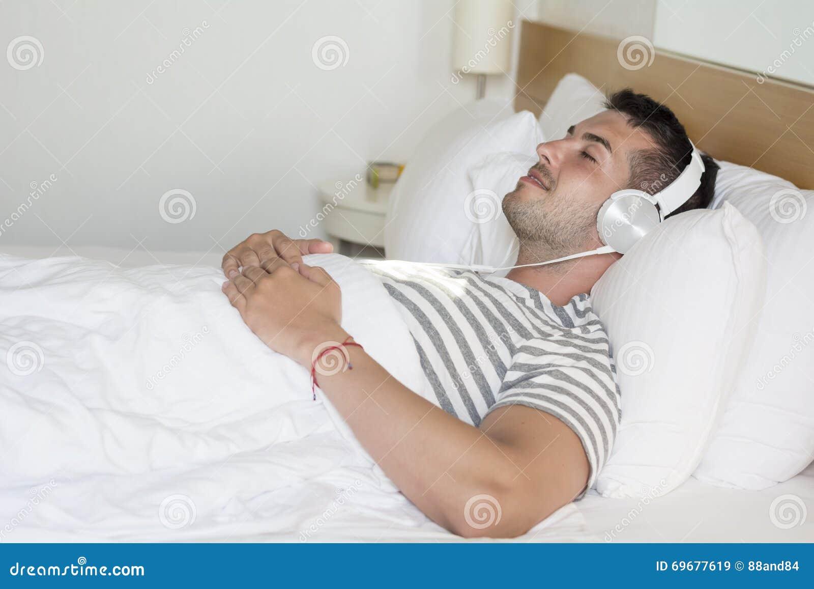 Lit Pour Jeune Homme jeune homme dormant dans la musique de écoute de lit image