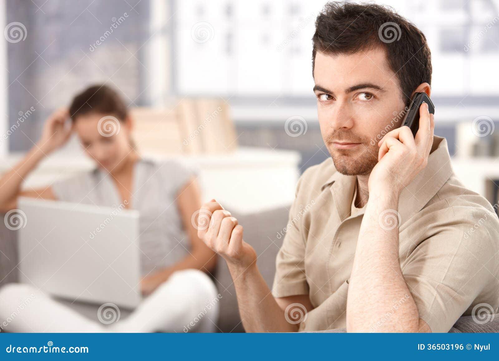 Jeune homme employant la femme de mobile à la maison à l arrière-plan