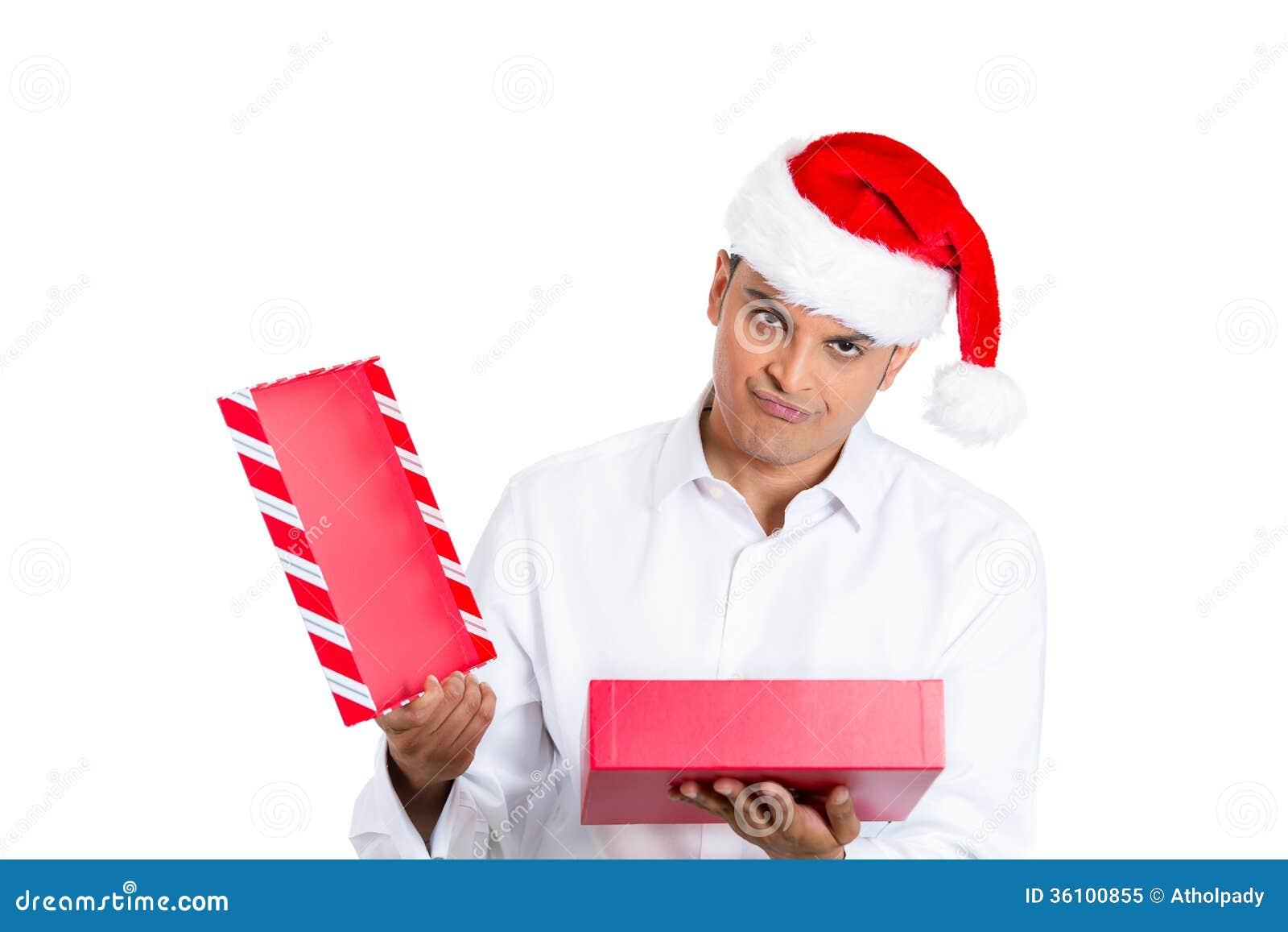 Jeune homme en cadeau rouge d ouverture de chapeau du père noël et très bouleversé